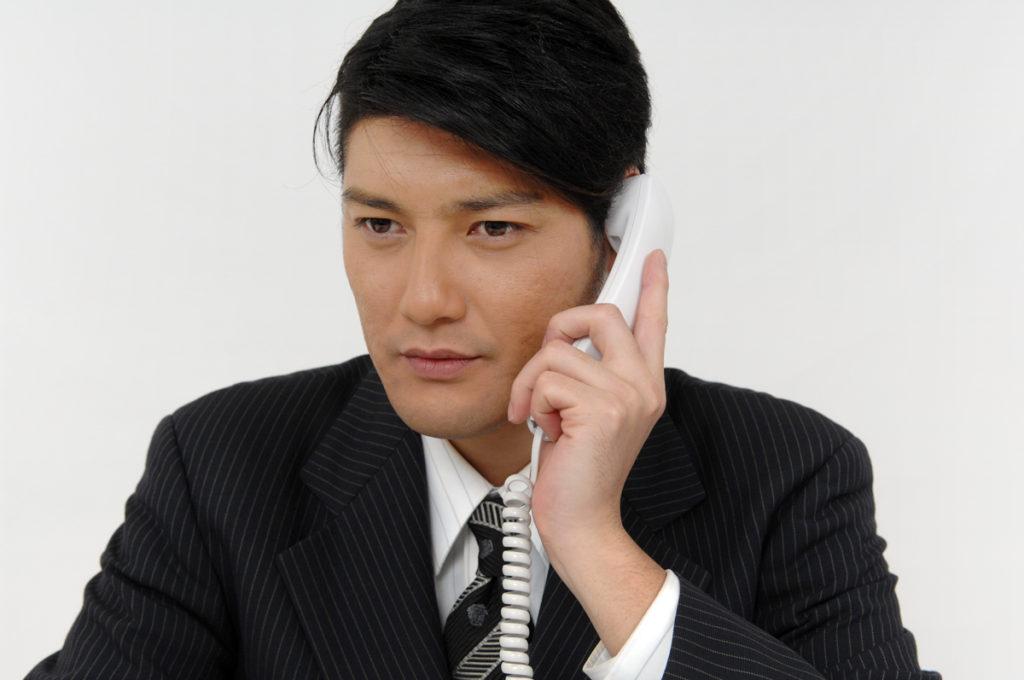 ビジネスフォンで電話する男性